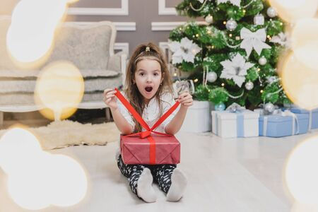 Full-body, forefront blurred photo of cute child sitting in lotos position with a Christmas present in hands, finding out what is inside.