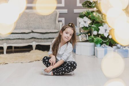Angelic child daughter is sitting in lotos position on the carpet near glittering Christmas tree. Bokeh lights forefront. Banco de Imagens