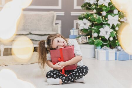 Light photo of cute kid sitting with gift in hands, like a little gnome in christmas decorated room. Stock Photo