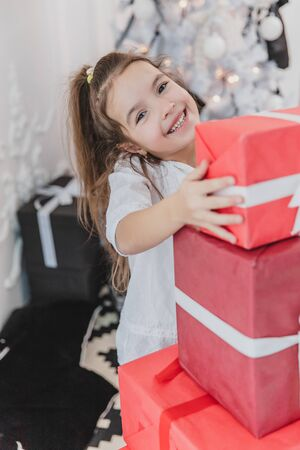 Cute kid prepared a pile of red gift boxes with white ribbons for her friends and family.