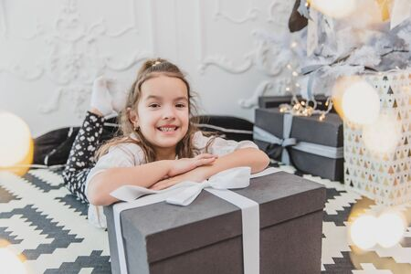 Sleepy but happy child in christmas pajamas is laying on the floor under the christmas tree, keeping hands on the large present. Banco de Imagens