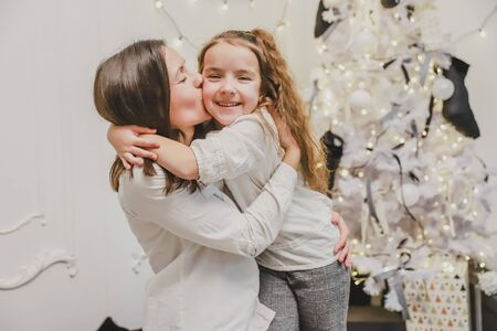 Closeup photo of young mother, holding daughter in her hands. They are hugging and kissing one another near fir-tree, enjoying time together.