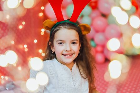 Bokeh lights from a Christmas garland on the forefront and cute little girl with reindeer antlers, looking at the camera, smiling in the evening at home.