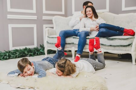 Lovely family members in red socks are meeting of new year. Sleepy children are laying on the white carpet.