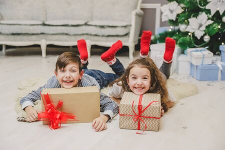 Careless, smiling small siblings enjoying Christmas time and presents, laying on the carpet under fir-tree.