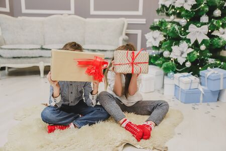 Careless sister and brother enjoying Christmas time, hiding faces behind big giftboxes.