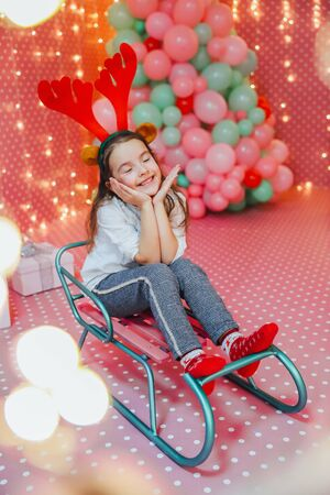 Cute little girl sits on the sledge in the pink room with baloons and bokeh garlands on the forefront. Banco de Imagens