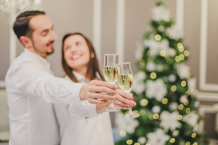 Toasting with champagne glasses against holiday lights and christmas tree.
