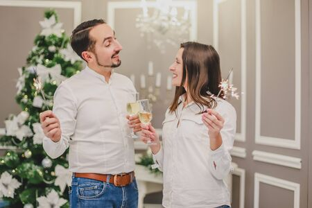 Shot of cool man and woman making wishes, with glasses of champange and bengal lights in their hands.