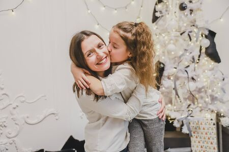 Cheerful mother and daughter near beautiful decorated Christmas tree, cuddling. Banco de Imagens