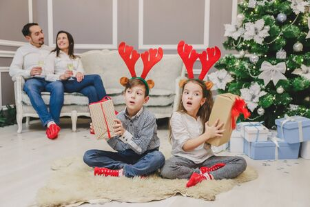 Full-body photo of cute children sitting in lotos position with a Christmas present in hands, finding out what is inside, while parents are sitting on the sofa, drinking champange.