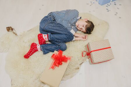 Lovely image of little boy sleeping on white carpet, among Christmas presenst, curling up.