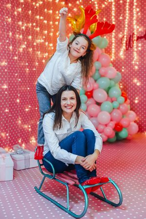 Young happy mother and her little toddler daughter making fun, imitating a sledge ride in a beautiful room decorated for new year. Banco de Imagens