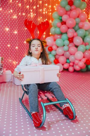 Child, present and sledge on the pink celebration background. Greedy child is frowning, keeping box close to her chest.