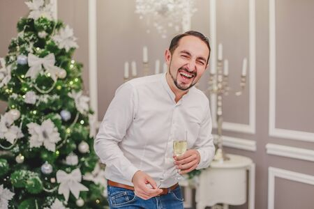 Handsome businessman is meeting new year with glass of champange, laughing desparately. Zdjęcie Seryjne