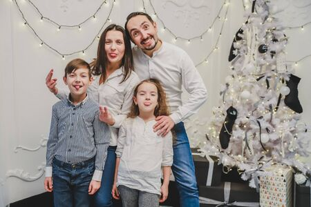 Funny photo of funky positive mom, dad and siblings posing, showing tongues and making grimaces on glittering new year background. Banco de Imagens