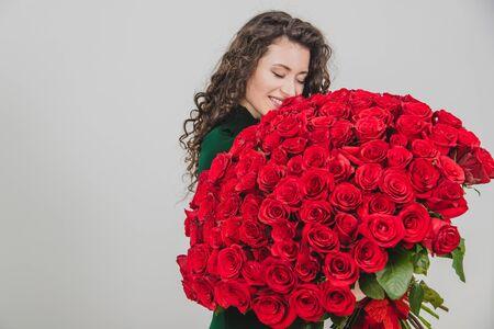 Linda chica morena rizada de pie, oliendo rosas rojas sobre fondo blanco.