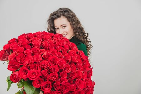 Cute curly brunette girl standing, smelling red roses over white background.