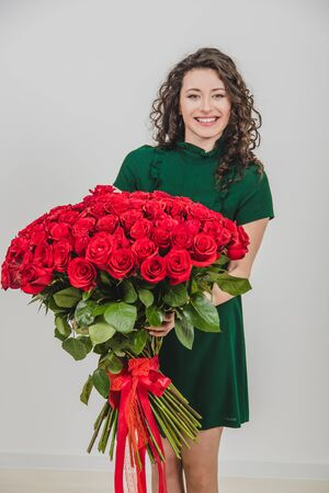 Beautiful young woman with rose bouquet, looking delighted and loved, over white background. Stock fotó