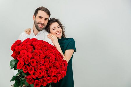 Concept of true love. Affectionate couple standing together, shining with happiness, holding gorgeous bunch of roses.