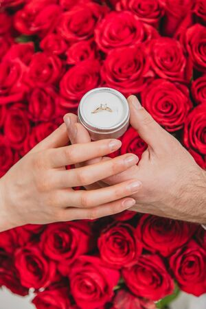 Bunch of red roses, wedding ring and love - all you need for marriage proposal.