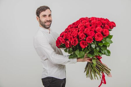 Good-looking man standing with large bouquet of red roses tied with stripes, smiling. Stockfoto