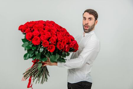 Portrait of a young man with a red roses bouquet, looking confused, because he dont know how to make a proposal.