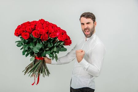 Good-looking man standing with large bouquet of red roses tied with stripes, cheching his fist, like a macho, because his girlfriend said agreed to marry him.