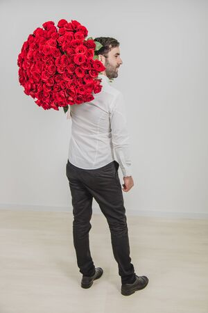 Portrait of confident man in formal clothes, standing back to the camera, carring a bouquet of red roses on his shoulder.