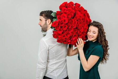 Romantic young man and woman posing with a bouquet of red roses over white background. Stockfoto