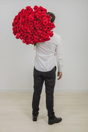 Full-length portrait of confident man in formal clothes, standing back to the camera, carring a bouquet of red roses on his shoulder.