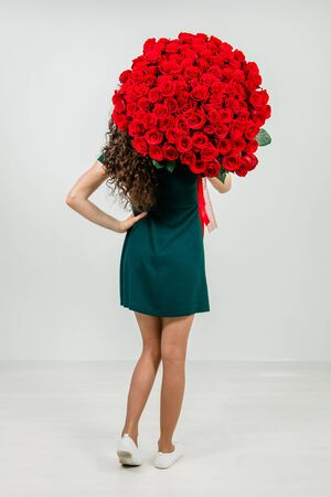 The girl in a tender dress is standing with her back and holding a bouquet of red roses on her shoulder on the white background.