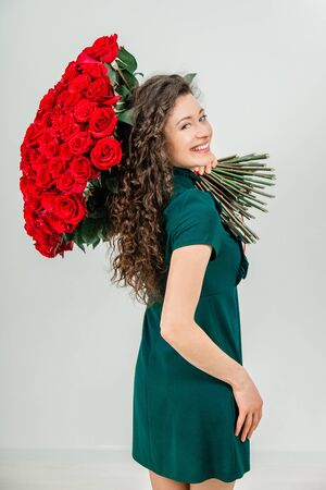 Enthusiastic woman isolated over a white background, keeping huge bouquet of tender flowers on her shoulder and looking at the camera fully delighted. Stockfoto