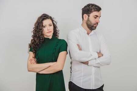 Portrait of young couple after argument standing separately with hands folded over white background.