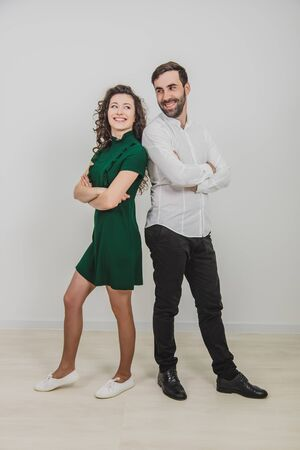 Cheerful man and woman with crossed hands standing back to back together, looking confident, on the white background.