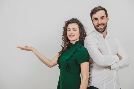 Group of two people on white background standing back to back, man folded hands, woman pointing her hand to the side, palm opened with copyspace for a product.