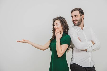 Copyspace shot of couple presenting something over white background and looking at it shocked and amazed.