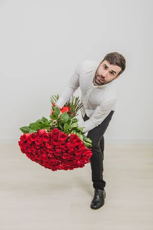 Young man holding heavy roses bouquet, leaning to the camera, frowning, looking unhappy.