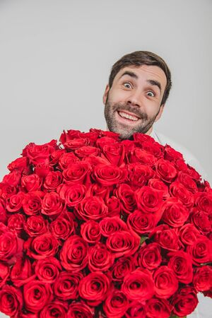 Funny expressive man isolated on white background, holding huge bunch of roses and looking from behind them with really silly face expression and grin.