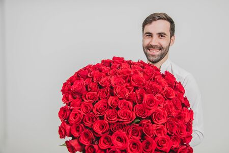 Man looking excited, standing with bunch of delicate flowers for his wife, over white background.