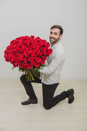 Full Length shot of handsome young man holding roses and looking at camera, smiling while kneeling, against white background.