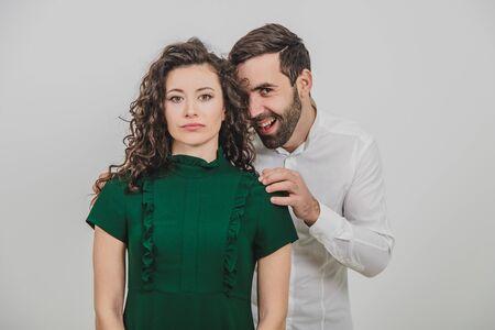 Der Mann grinst, als ob er sich ausgedacht hätte, seiner Freundin etwas Ungewöhnliches und Hinterhältiges anzutun, das ihm ruhig und unbeweglich gegenübersteht.
