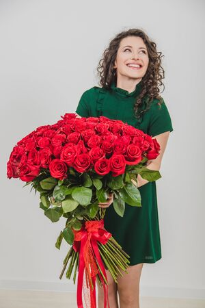 Cheerful young lady with long wavy hair being excited to get bouquet of red roses on Womens day isolated over white background. Stockfoto