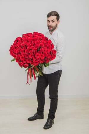 Elegant bearded man holding a bouquet of red roses for valentines day, isolated on white background. Stockfoto