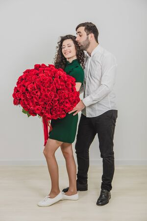 Full-body portrait of man and his woman standing over white backgroud with roses in his hands. Man kisses his woman on head, after she says yes to his proposal. 版權商用圖片
