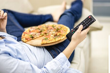 Concept leisure after hard day. Woman is switching TV channels with a zapper. Stockfoto