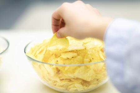 Concept take potato chips with you to watch movie. Close up. Blurred background.