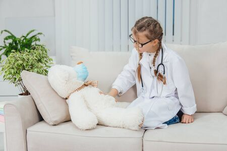 Medicine concept. Shot of kid in doctor coat and teddy-bear.