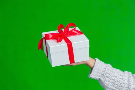 Present for special event concept. Close up of female hand holding white gift box tied with red ribbon isolated on green background.