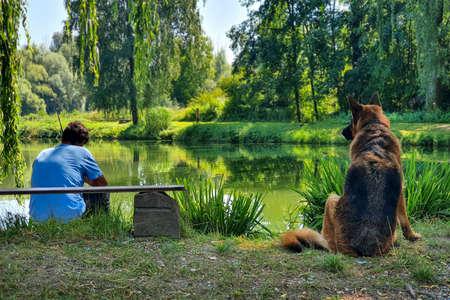 The dog and the owner fishing, lake, German shepherd Standard-Bild